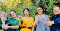 Four women standing in a line against a row of trees. Three of the women are holding self-testing kits, and one woman is holding a toddler who is holding a self-testing kit. They are smiling wearing colourful clothes, holding the kits out toward the camera