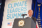 "President Biden stands in front of a podium with a sign reading ""Climate leaders summit behind him."""