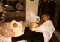 a sleeping baby, white terrier dog, and woman on a bed together
