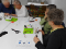 Four older adults split into pairs, seated at a table working on an activity with a Grove Arduino toolkit.