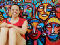 A woman smiles in front of a painted mural of many colorful faces