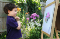 Young boy admiring his painting of a flower near him in the garden