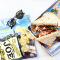 a sandwich, a bag of chips, a magazine, and sunglasses on a table