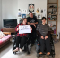 Three people in their home smiling. Two are in wheelchairs and one holds a sign for safe, accessible housing.
