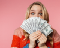 A wide-eyed woman holds up hundred dollar bills in front of her face like a hand of cards.