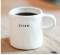 "Coffee cup with the word ""Begin."""