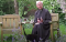 A priest sits in a lovely garden as a cat approaches him