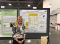"The author stands in front of a poster on ""Consumer Discussion of DTC Genomic Testing Results with Primary Care Providers"""