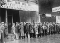 Photo of Great Depression breadline. A long line of men standing outside, wearing tattered coats.