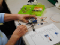 An older adult's hands working with a Grove Arduino Toolkit with wires coming out of the shield to connect to components.