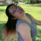 Desiree Leong stands sideways smiling. She is standing on a grass lawn.