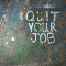 Quit Your Job spray painted on a wood floor.
