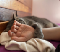A grey polydactyl cat laying on a bed beside the arm and hand of a person, with a grey paw draped over the person's wrist.