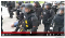 Still frame of a protestor bleeding on the ground surrounded by a dozen officers in riot gear.
