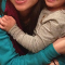Cropped family photo of a woman holding a child