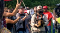 A man in a camo baseball cap uses a megaphone to shout at a reporter in body armor who has turned away to leave