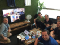 The FanDuel Compliance team sits together in a meeting room, with remote team members on a TV screen behind them.