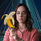 Image from the Netflix show Sexify. A white blue eyed brunette stares at a vibrator, a look of challenge in her eyes. The vibrator image is covered by a banana.