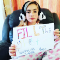 """A young girl with panda earmuffs holds a sign saying """"Fill the Ghost Houses"""""""