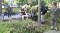 Two men armed with assault rifles sit in a park and glare at the cameraperson