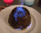 A Christmas pudding sits on a white plate with a blue flame rising out of the top.