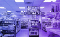 Purple-filtered image of the inside of a pharmacy store. There is a TV with surviellance footage in the middle.