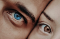 Extreme closeup of two people's faces pressed cheek-to-cheek. The older man has blue eyes and the young woman has brown.
