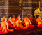 Buddhist monks in front of the altar in Bangkok, Thailand