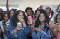 A group of teenagers look extra excited as they whip out their phones to take videos and photographs of a performer.