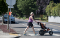 A woman pushing a stroller walks from a curb cut onto a crosswalk in the street
