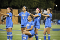 4 players on UCLA women's soccer team toudh each other's shoulder while 1 player of color kneels
