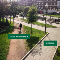 """A photo of a courtyard between buildings. There is a paved pathway that's labeled """"DESIGN,"""" but no one is using it. There's a more direct dirt pathway that's labeled """"USER EXPERIENCE"""" and someone is walking on it."""