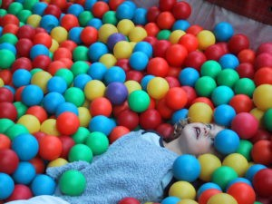 female child in a ball pool - illustrating autism article on spectra.blog