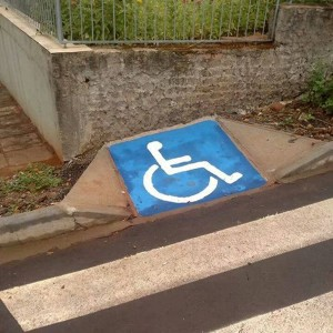 Curb cut painted with blue wheelchair symbol that ends at a vertical wall