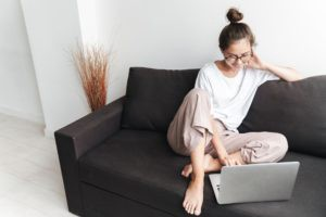 Image of smiling brunette woman typing on laptop while sitting on sofa