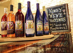 """A lineup of mead bottles in front of a chalk board that reads, """"Honey Wine Tastings; $5.00 tasting fee. Beelicious!"""""""