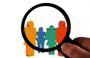 people figures viewed through a magnifying glass