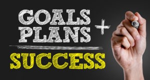 Hand writing the text: Goals + Plans = Success