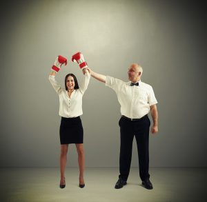 Woman with boxing gloves and a referee holding up her glove