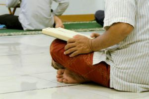 partial view of cross-legged person on floor holding an open book