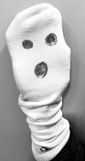 White tube sock with a face drawn on the bottom