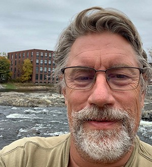 Selfie image of man with glasses, grey hair, mustache and beard, River and factory in background