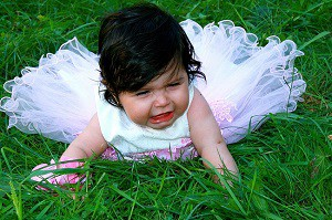 Little girl in white dress on ground crying angrily