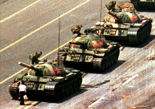Lone man standing in front of a line of tanks