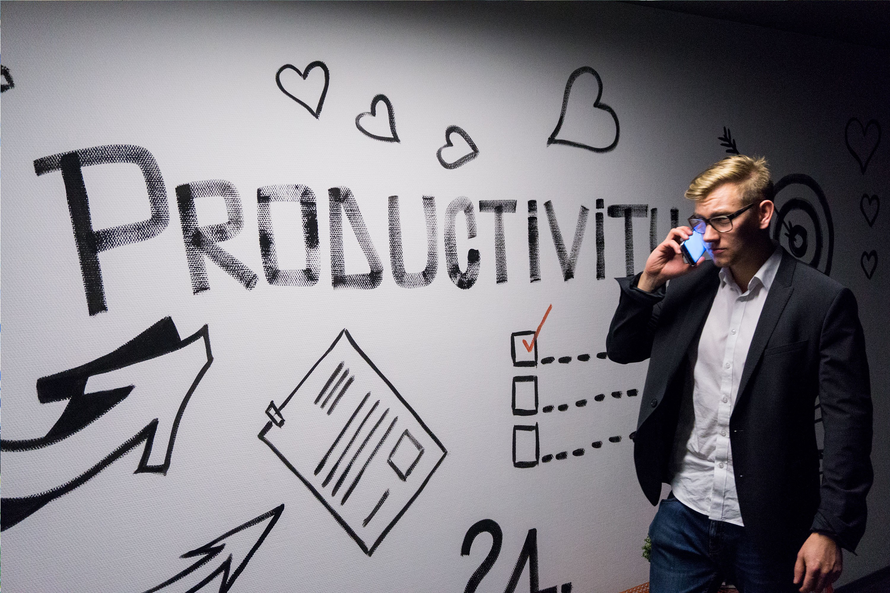 man on phone in front of wall display about productivity