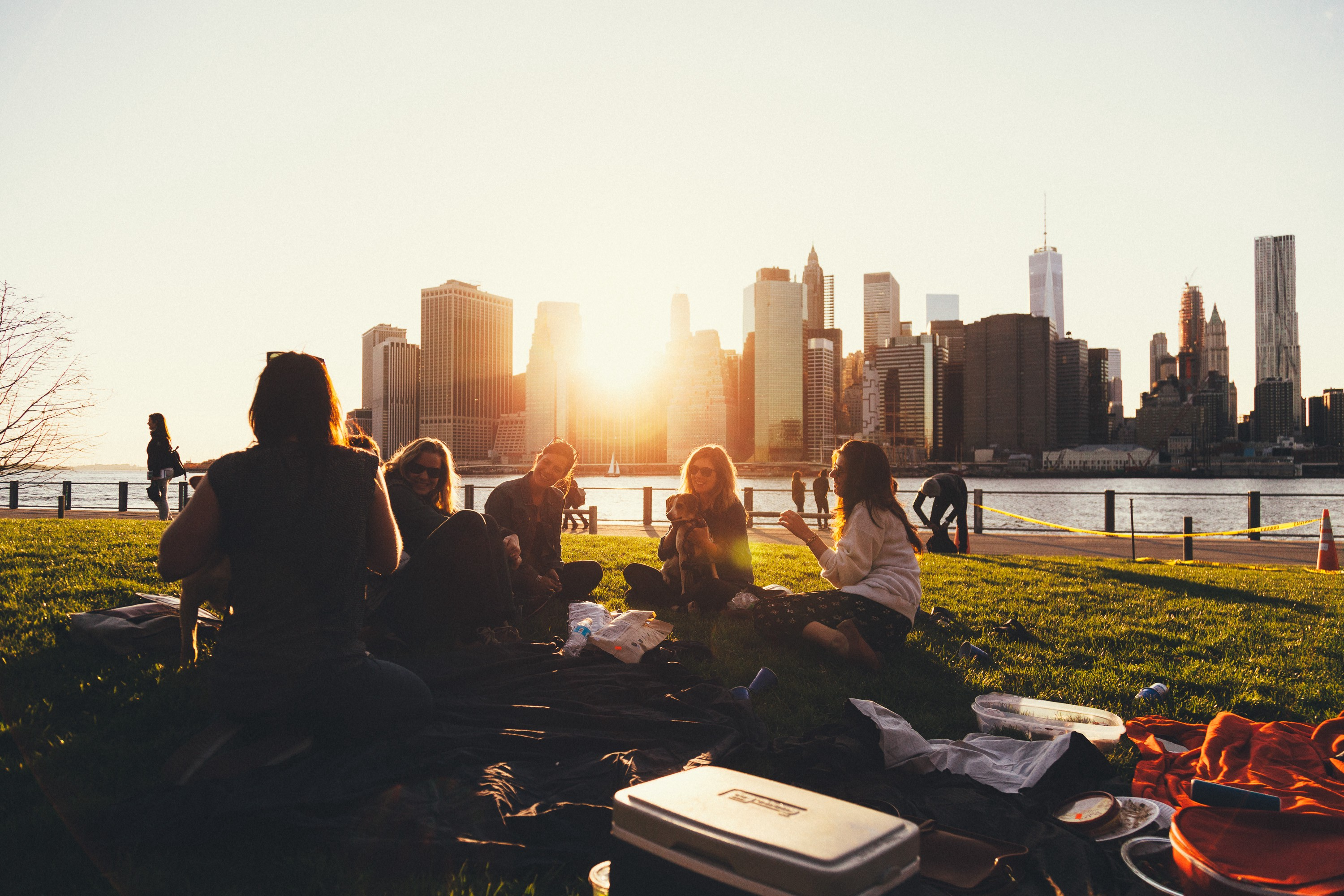 A group of mothers sitting together in a park. A city skyline and sunset are in the background.