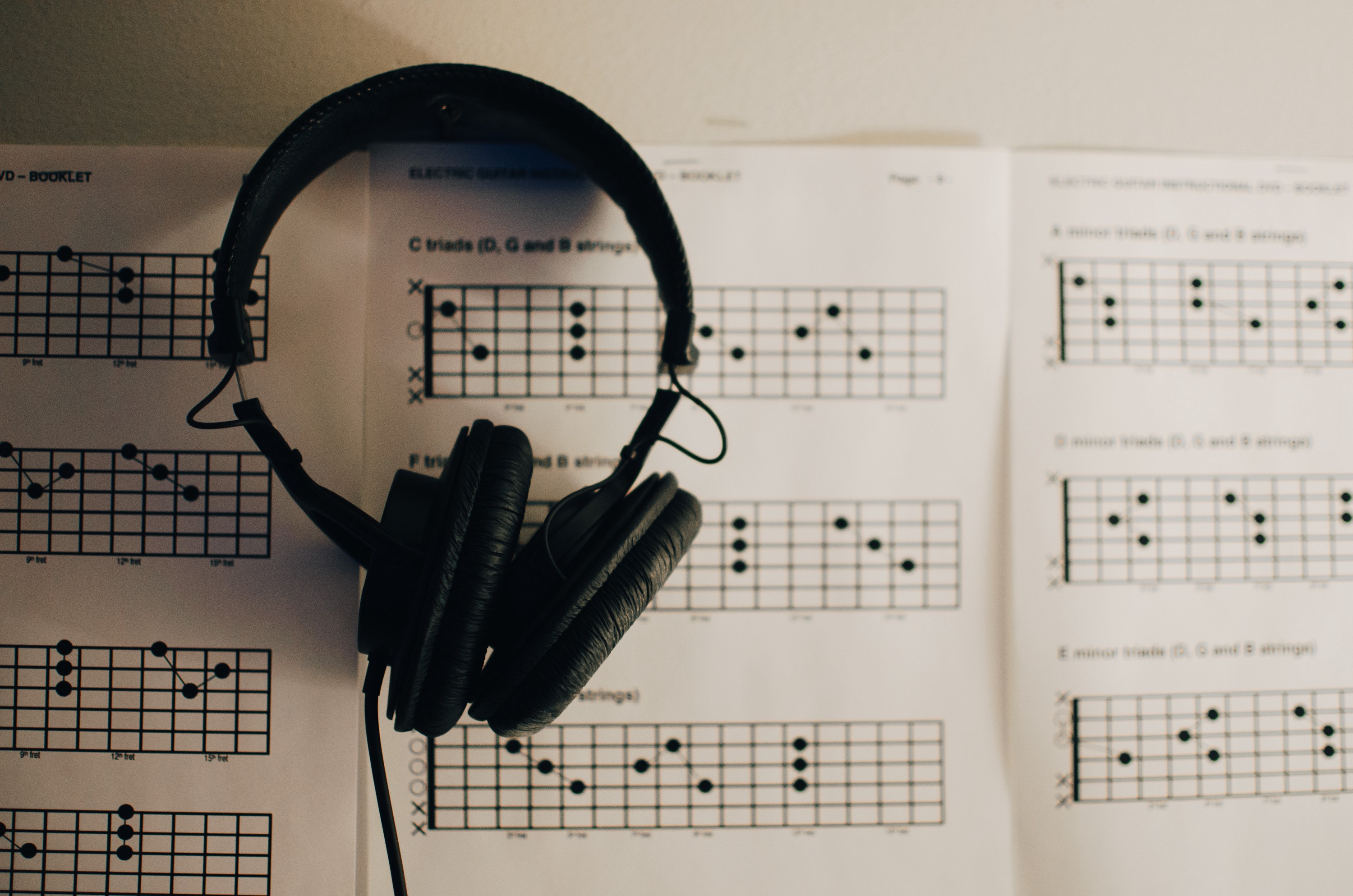 A pair of black headphones lies on top of an open book of musical notation.