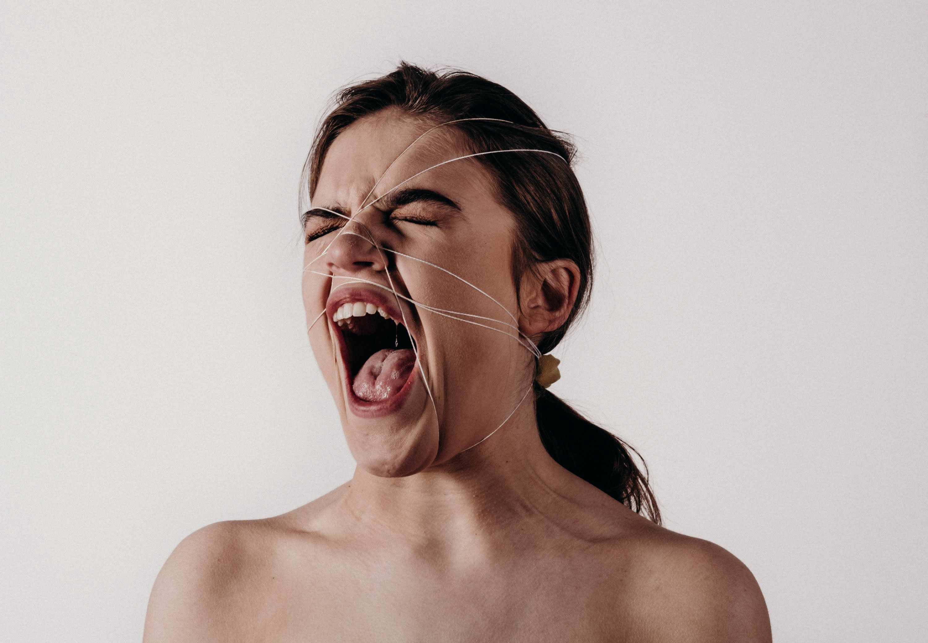 Lady with something tied around her face, naked and screaming.