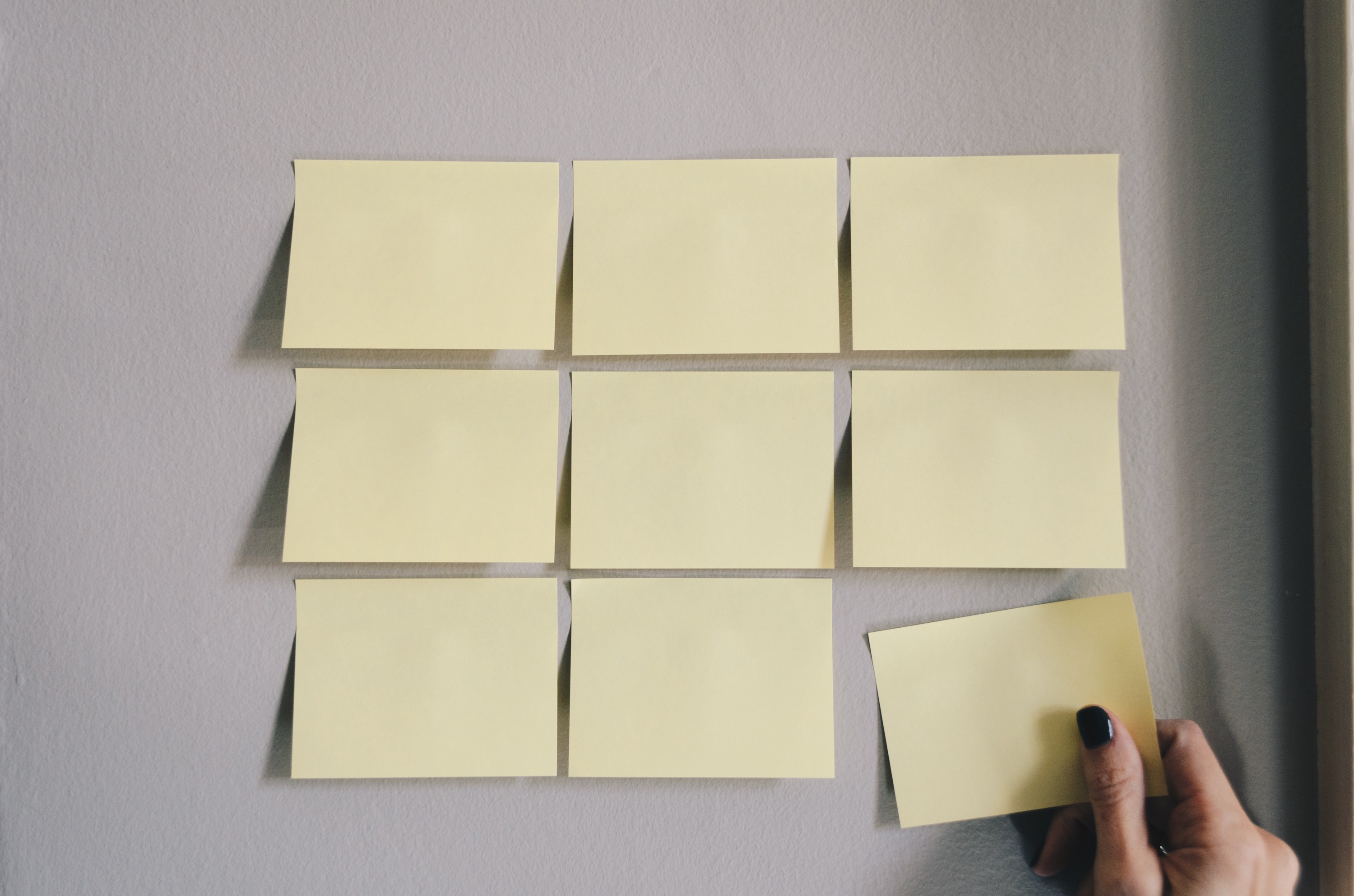 Nine Post-Its attached to the wall with a woman's hand grabbing one