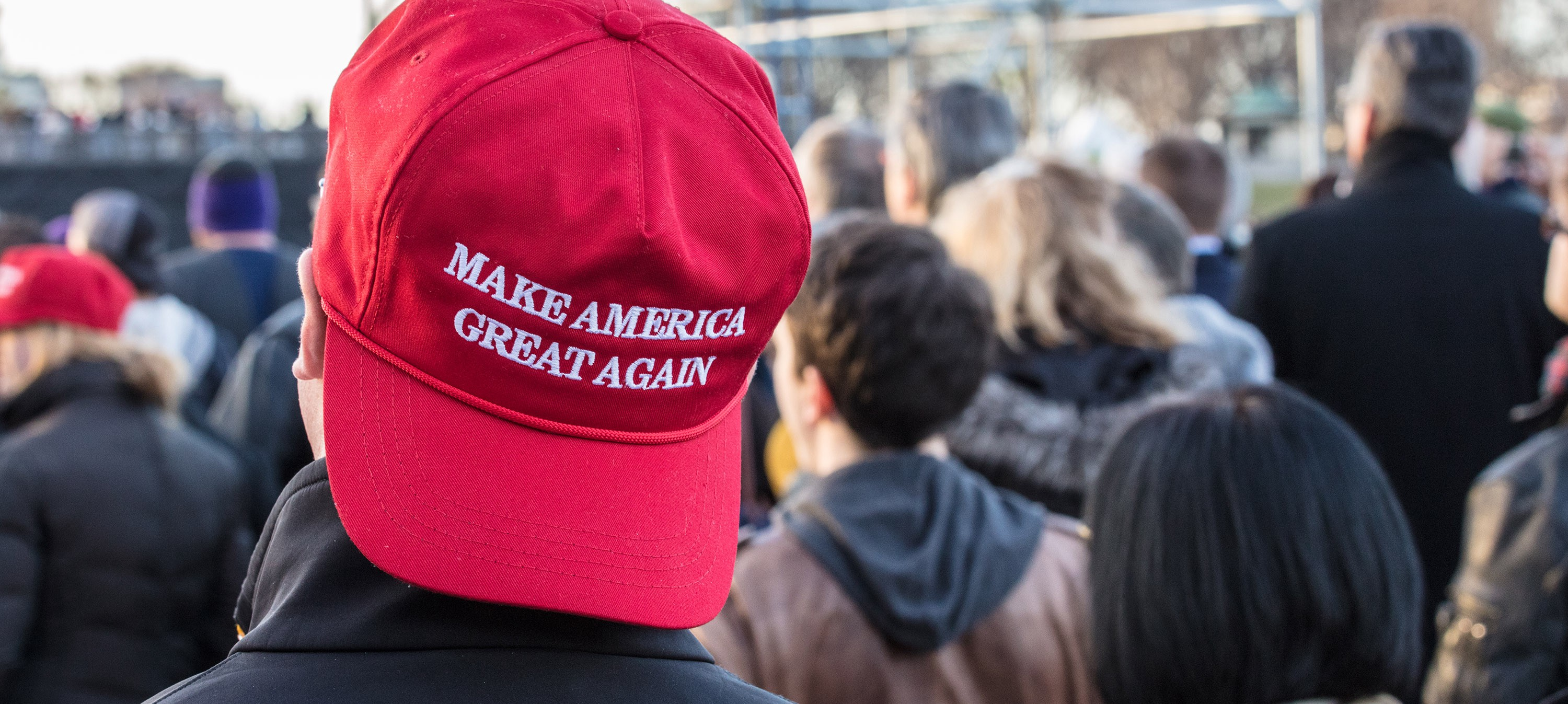 "A young man at a Donald Trump rally wears a ""Make America Great Again"" hat."